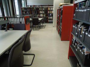Blick in den Lesesaal des Archivs mit Bücherregalen und Tischen